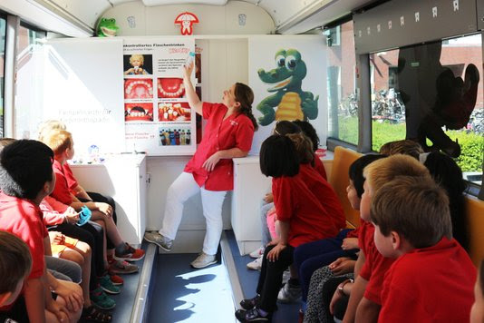 Eerste schoolklas wordt in de Krockybus geïnformeerd over gebitsonderhoud door Dr. Christina von Massow. Foto: Tess Fluit