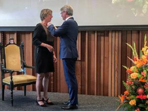 Iet van Albada krijgt de koninklijke onderscheiding opgespeld door burgemeester Lucas Bolsius van Amersfoort.
