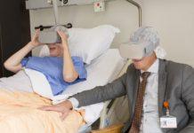 Foto: een patiënt (links) en bestuurder Peter Langenbach (rechts) genieten samen zichtbaar van een virtual reality beleving